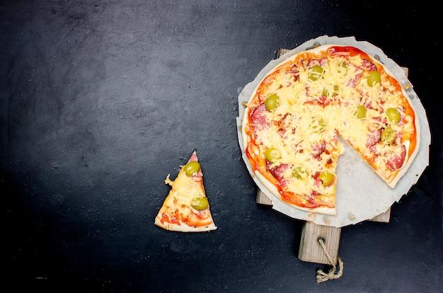 Savoureuse pizza aux épices et olives sur fond noir