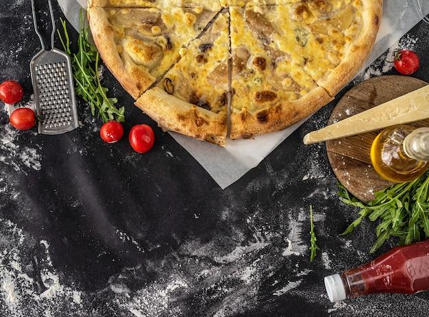 Savoureuse pizza sur une surface noire saupoudrée de farine, vue d'en haut