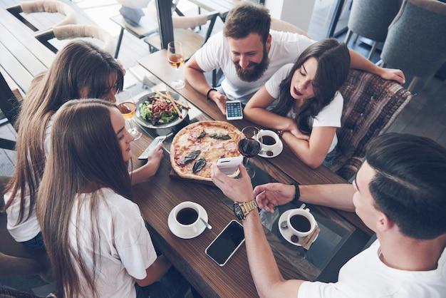 Savoureuse pizza sur la table, avec un groupe de jeunes souriants se reposant dans le pub.