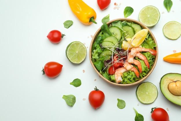 Savoureuse salade de crevettes et ingrédients sur fond blanc