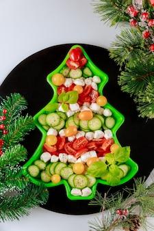 Savoureuse salade de légumes en forme de sapin de noël avec décoration.