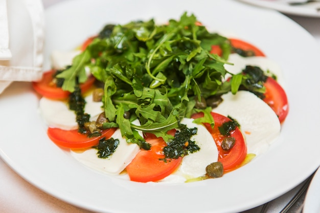 Savoureuse salade de tomates, de fromage et de roquette sur une plaque blanche dans le restaurant
