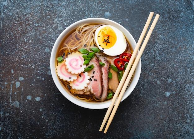 Savoureuse soupe de nouilles japonaises ramen dans un bol en céramique blanche avec bouillon de viande, porc tranché, narutomaki, œuf au jaune sur fond de pierre rustique. plat traditionnel du japon, vue de dessus, gros plan, concept