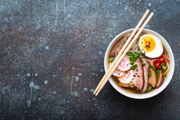 Savoureuse soupe de nouilles japonaises ramen dans un bol en céramique blanche, bouillon de viande, porc tranché, narutomaki, œuf au jaune sur fond de pierre rustique. plat traditionnel du japon, vue de dessus, gros plan. espace pour le texte