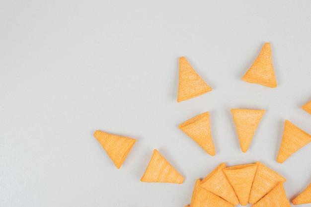 De savoureuses chips croquantes sur une surface grise