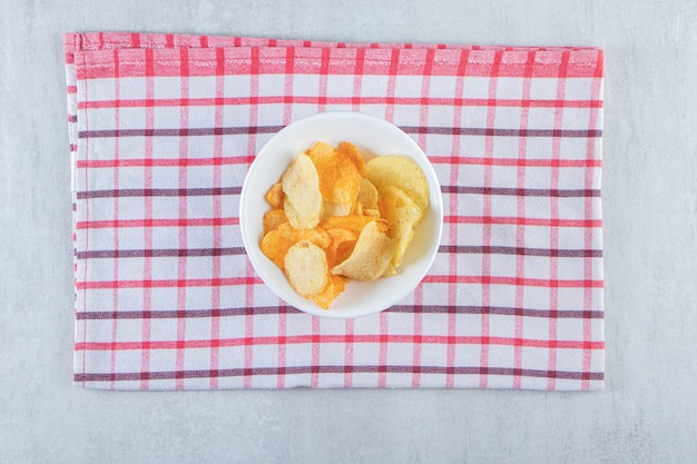 De savoureuses chips croustillantes placées dans un bol blanc avec une nappe.