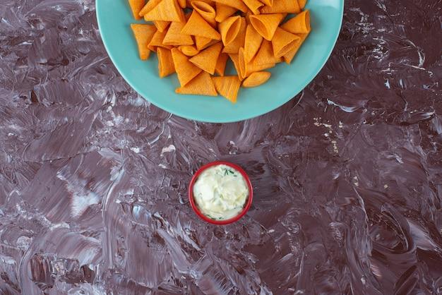De savoureuses chips épicées sur une assiette à côté de yaourt, sur la table en marbre.