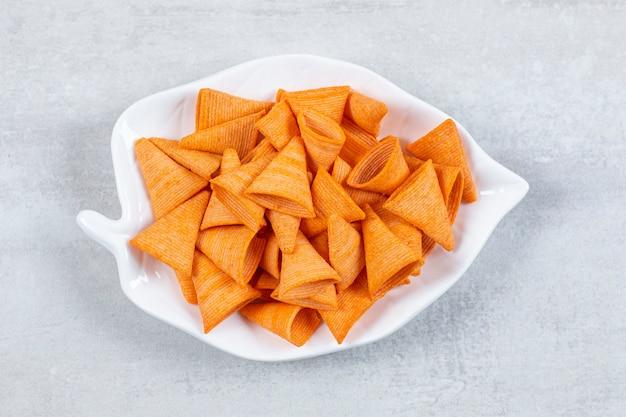 Savoureuses chips triangulaires sur plaque en forme de feuille.