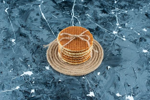De savoureuses gaufres sur un dessous de plat, sur la table bleue.