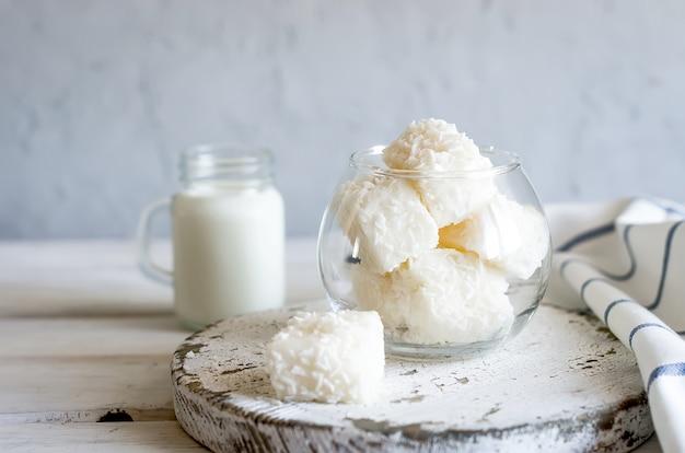 De savoureuses guimauves blanches ou des bonbons en flocons de noix de coco et une tasse de lait