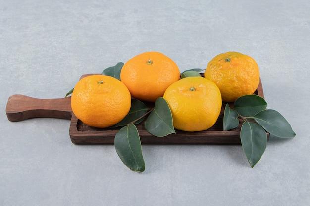 Savoureuses mandarines fraîches sur planche de bois.