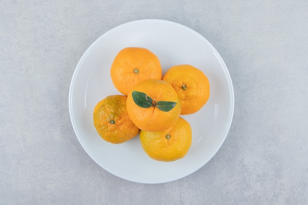 De savoureuses mandarines fraîches sur plaque blanche