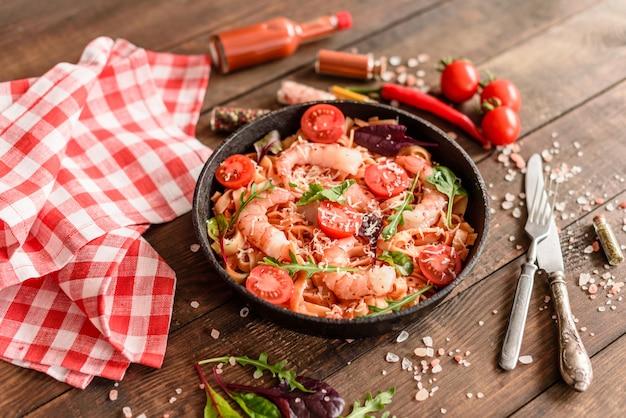 Savoureuses pâtes aux crevettes et à la tomate sur une poêle à frire