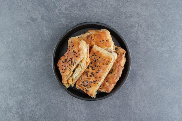 De savoureuses pâtisseries farcies sur plaque noire.