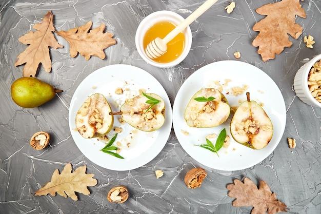 Savoureuses poires rôties au miel et aux noix sur des assiettes blanches sur fond gris table.