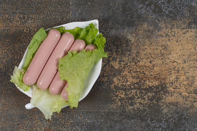 Savoureuses saucisses bouillies et laitue sur une assiette en forme de feuille.