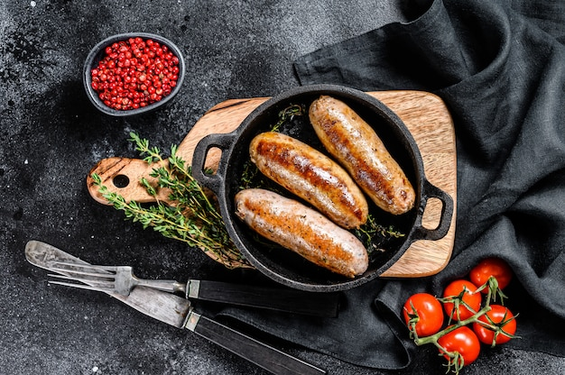 Savoureuses saucisses maison dans une poêle. viande de porc, de boeuf et de poulet. fond noir. vue de dessus