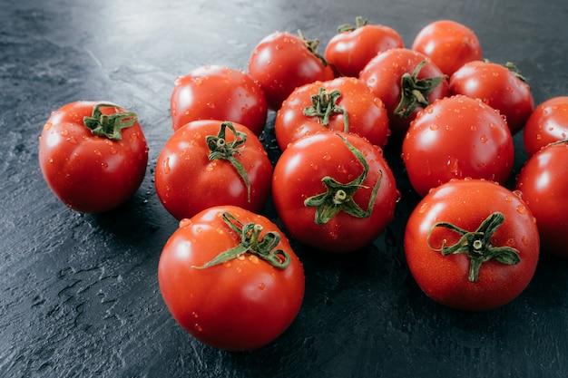 Savoureuses tomates fraîches mûres rouges avec de l'eau tombe sur fond sombre. légumes cueillis au jardin. nourriture crue domestique. photo en gros plan.