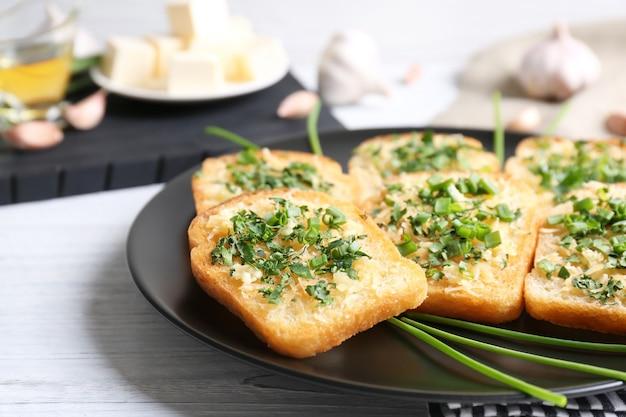 De savoureuses tranches de pain à l'ail, au fromage et aux herbes sur une assiette
