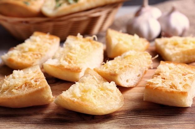 De savoureuses tranches de pain à l'ail et au fromage sur une planche à découper en bois