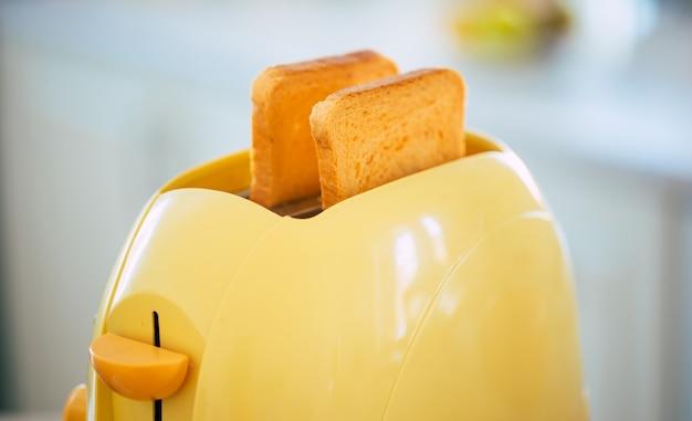 De savoureuses tranches de pain grillé fraîches du grille-pain jaune sur la belle table de cuisine à la maison