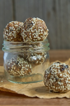 Savoureuses truffes de protéines crues végétaliennes ou boules d'énergie aux pruneaux, graines et noix dans un pot en bois