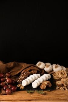 Savoureux aliments crus sur une table en bois contre du papier peint foncé