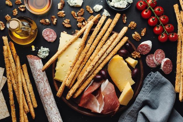 Savoureux apéritifs italiens classiques sur table sombre. vue d'en-haut.