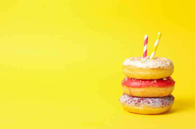 De savoureux beignets avec des pailles sur fond jaune, espace pour le texte