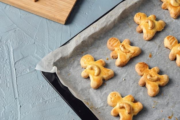 De savoureux biscuits de noël faits maison, des biscuits aux noix de cajou fraîchement cuits sous la forme d'une poupée sur la table
