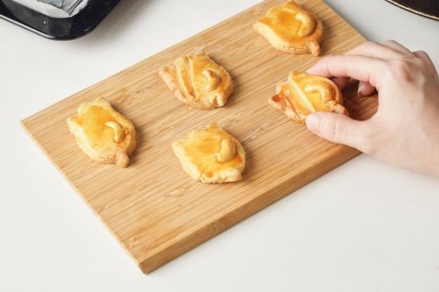 De savoureux biscuits de noël faits maison, des biscuits aux noix de cajou fraîchement cuits sous la forme d'une poupée sur le tableau blanc
