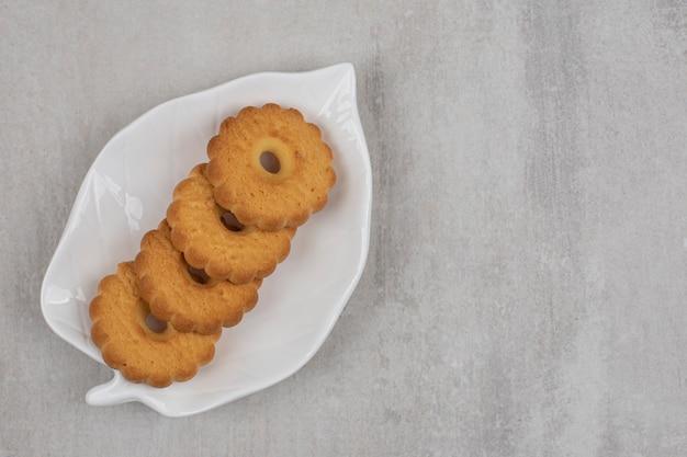 De savoureux biscuits sucrés sur une assiette en forme de feuille.