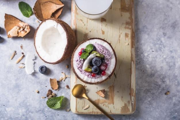 Savoureux bol d'açaï smoothie appétissant à base de mûres et de baies sauvages. servi dans un bol de noix de coco. concept d'alimentation saine de vie saine. dessert glacé belle crème.