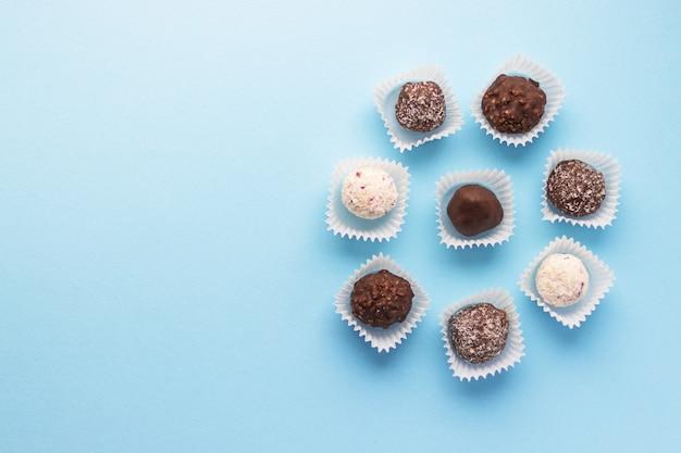 De savoureux bonbons au chocolat en forme de boule emballés dans de petits paniers en papier sur fond bleu. dessert romantique de la saint-valentin. délicieux sucré. style minimaliste. mise à plat, vue de dessus avec copie scape.