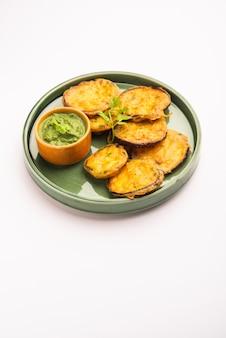 Savoureux brinjal pakora ou beignets d'aubergines croustillants, collation indienne à l'heure du thé servie avec chutney vert