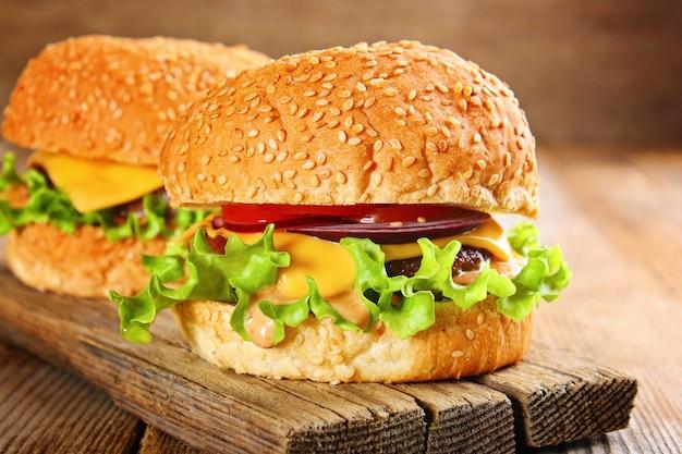 Savoureux burger maison composé de petits pains, de pâtés, de salade, d'oignons rouges et de tomates