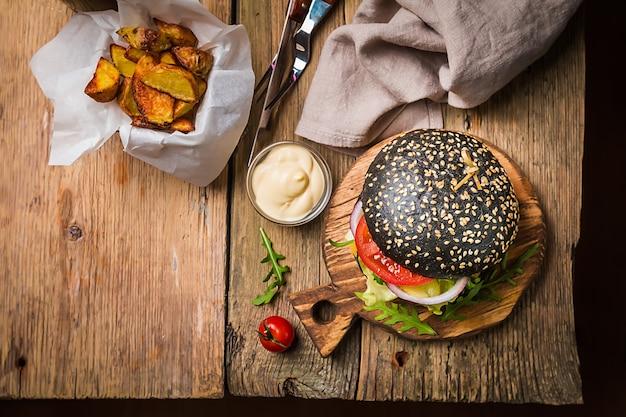 Savoureux burger noir de boeuf classique grillé avec laitue et sauce mayonnaise sur une table en bois rustique, vue de dessus avec copie espace