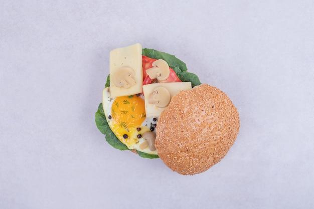 Savoureux burger avec tomate, fromage, laitue sur blanc.