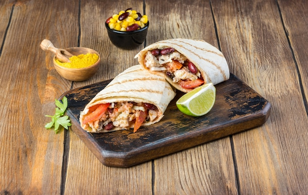 Savoureux burrito mexicain avec légumes, salsa épicée et citron vert