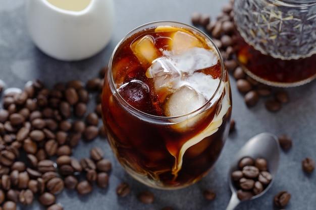 Savoureux café glacé rafraîchissant avec des glaçons dans des verres sur fond clair. fermer
