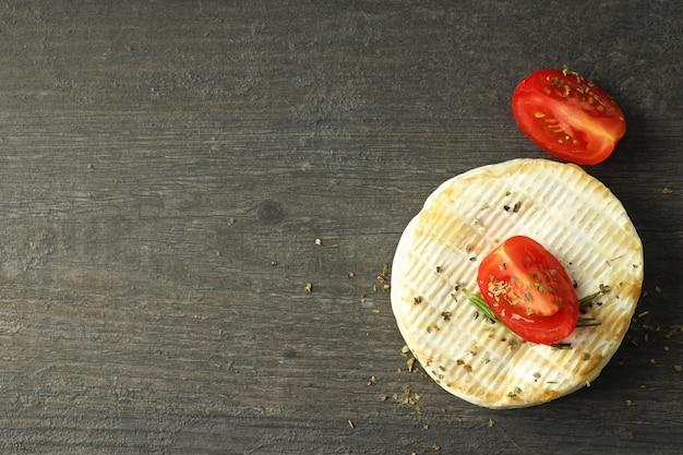 Savoureux camembert grillé sur fond de bois foncé.