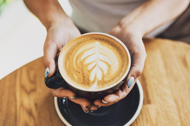 Savoureux cappuccino frais dans une tasse sur une table en bois. femme méconnaissable tenant la tasse dans les mains.
