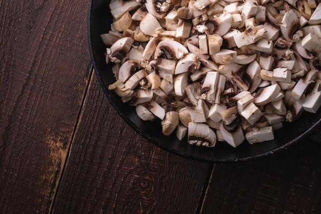 De savoureux champignons champignon hachés dans une poêle, des aliments non cuits en tranches, table en bois brun foncé, vue du dessus