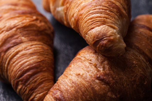 De savoureux croissants français sur une table en bois noir. grand dessert
