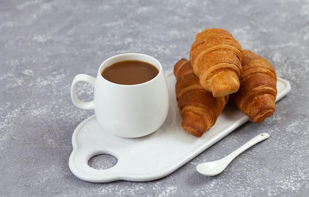 De savoureux croissants et tasse de café sur un plateau en céramique