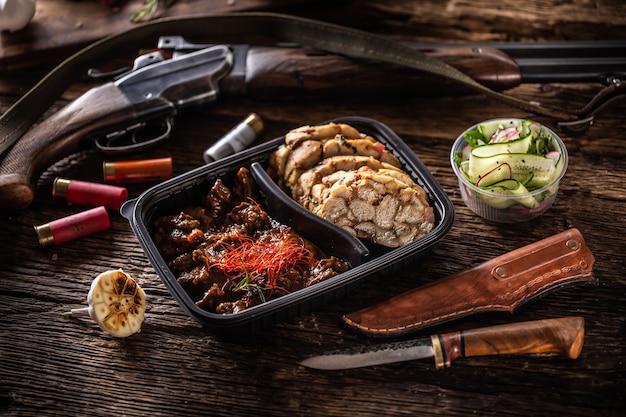 Savoureux et délicieux ragoût de goulasch de chevreuil emballé dans une boîte en plastique portable à emporter. la nourriture est servie avec des boulettes maison. le déjeuner est entouré d'un fusil de chasse rustique, de balles et d'un couteau de chasse.