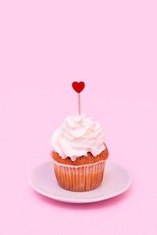 Savoureux gâteau avec fouet et ornement coeur sur baguette