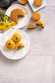 Savoureux gâteau de lune au jaune d'œuf cuit au four pour la fête de la mi-automne sur fond de table en ciment clair. concept de cuisine traditionnelle chinoise, gros plan, espace de copie.