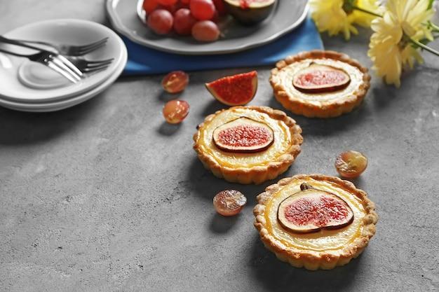 De savoureux gâteaux aux figues avec des raisins et des fleurs fraîches sur fond gris