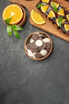 De savoureux gâteaux coupent des oranges avec des biscuits sur une planche à découper sur tableau noir